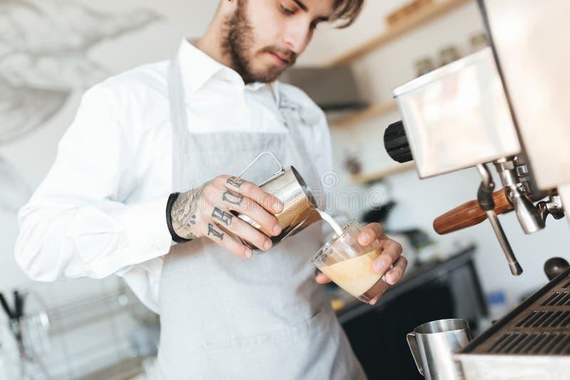 Jonge barista die kop van verse koffie maken bij barteller in koffiewinkel stock afbeelding