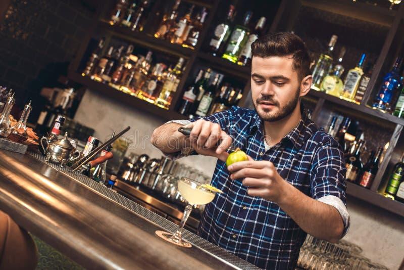 Jonge barman die zich bij geconcentreerde schil bevinden van de bar de tegen scherpe kalk stock foto