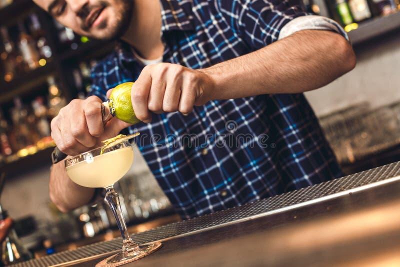Jonge barman die zich bij schil bevinden die van de bar de tegen scherpe citroen blij glas van tonisch close-up verfraaien royalty-vrije stock afbeelding