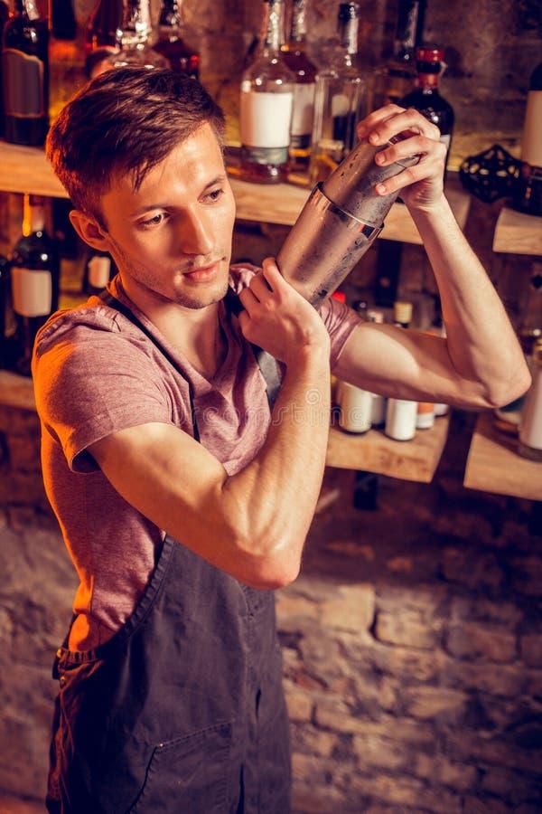 Jonge barman die zwarte schort dragen die cocktail maken royalty-vrije stock afbeelding