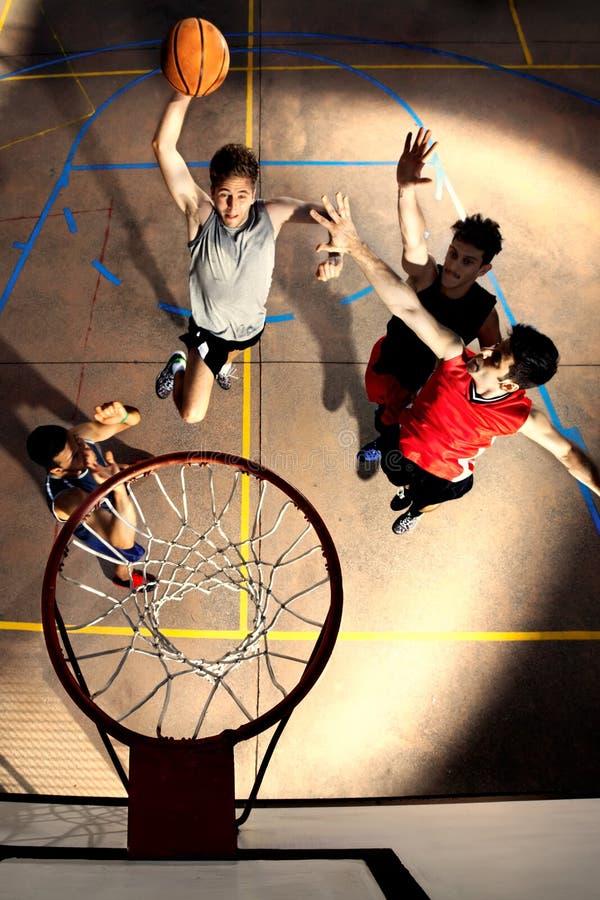Jonge basketbalspelers die met energie en macht spelen stock afbeeldingen