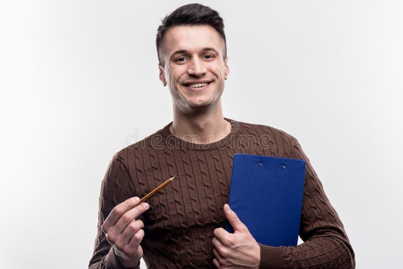 Jonge beambte die blauw logboekdossier en potlood in zijn handen houden royalty-vrije stock foto