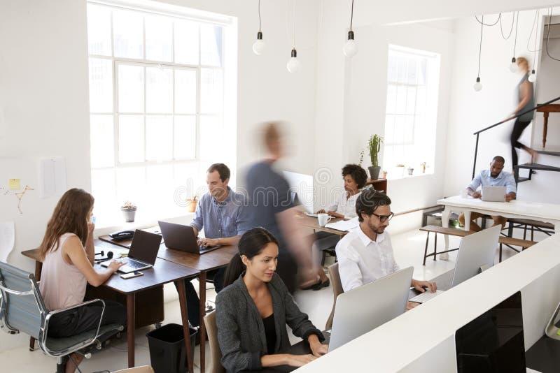 Jonge bedrijfscollega's die in een bezig open planbureau werken stock foto's