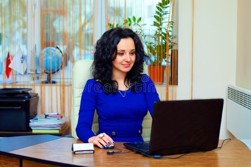 Jonge bedrijfsdievrouw op het werk in bureau wordt geconcentreerd royalty-vrije stock afbeelding