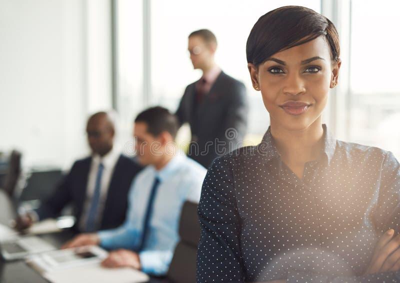 Jonge bedrijfseigenaar in bureau met werknemers stock afbeelding