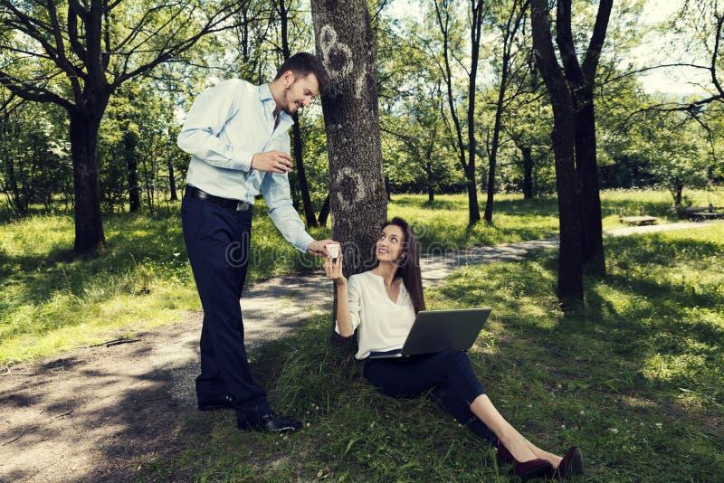 Jonge bedrijfsman en bedrijfsvrouw die en het drinken koffie in een openbaar park werken stock foto