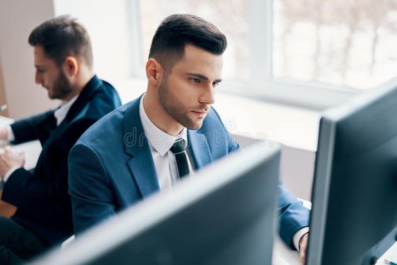 Jonge bedrijfsmens die aan computer in zijn werkplaats werken stock foto