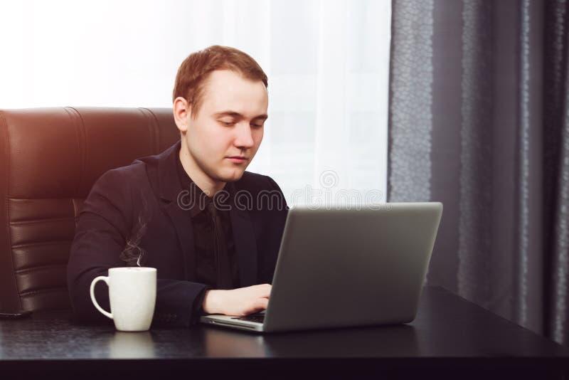 Jonge bedrijfsmens die aan laptop werkt Hete koffie dichtbij royalty-vrije stock foto's