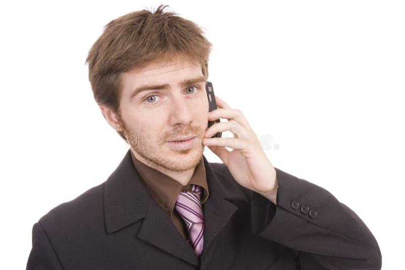 Jonge bedrijfsmens die een cellphone houdt stock foto's