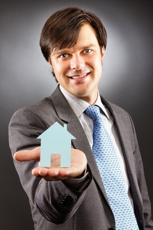 Jonge bedrijfsmens die een model van een huis op zijn palm houden royalty-vrije stock fotografie