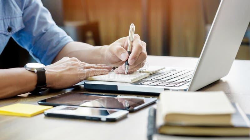 Jonge bedrijfsmens die in helder bureau werken, die laptop, writi met behulp van royalty-vrije stock fotografie