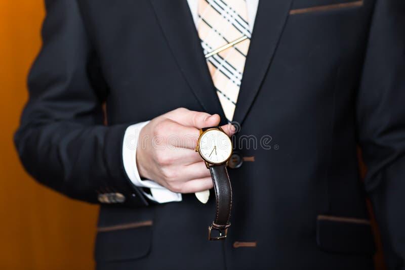 Jonge bedrijfsmens die horloge over wit bekijken stock foto