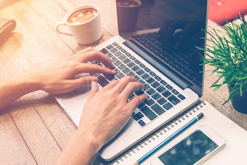 Jonge bedrijfsmens die laptop met behulp van die in koffiewinkel werken stock foto's