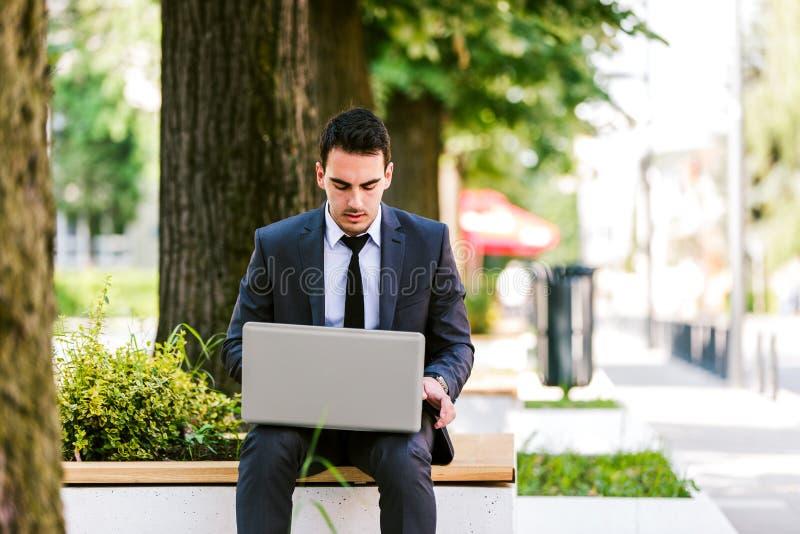 Jonge Bedrijfsmens die Laptop met behulp van terwijl het Zitten bij Bank stock foto's