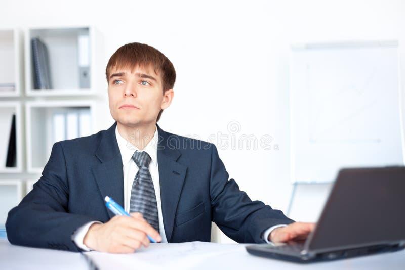 Jonge bedrijfsmens die op administratie in bureau schrijft stock afbeeldingen