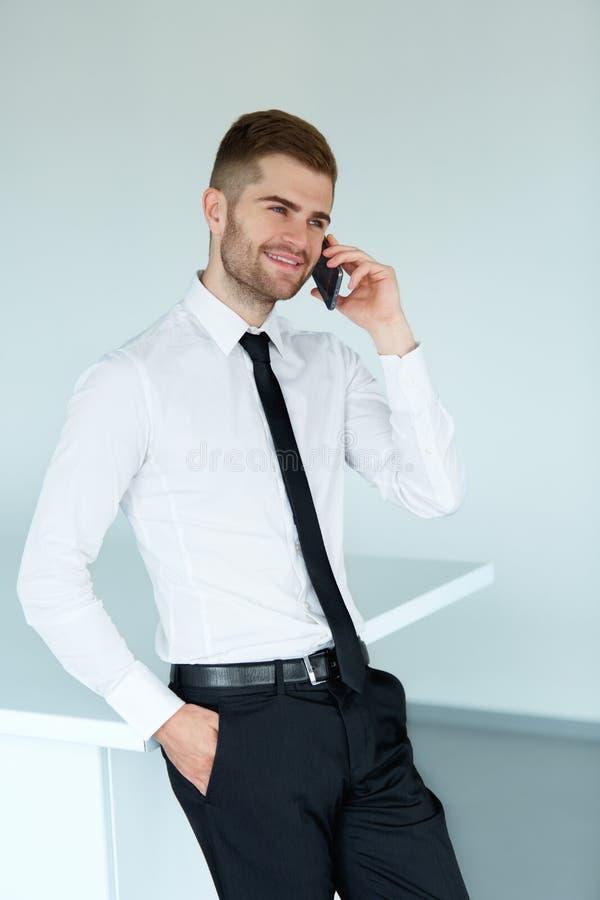 Jonge bedrijfsmens die op celtelefoon op modern kantoor spreken stock afbeeldingen