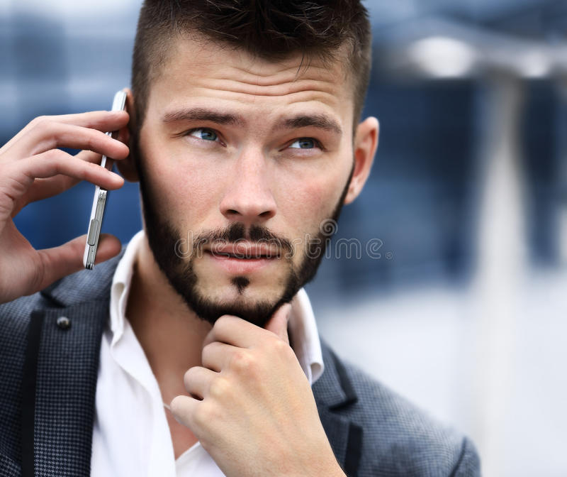 Jonge bedrijfsmens die op celtelefoon spreekt stock afbeelding