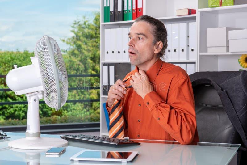 Jonge bedrijfsmens met ventilator bij zijn bureau in summerly heet o royalty-vrije stock afbeelding