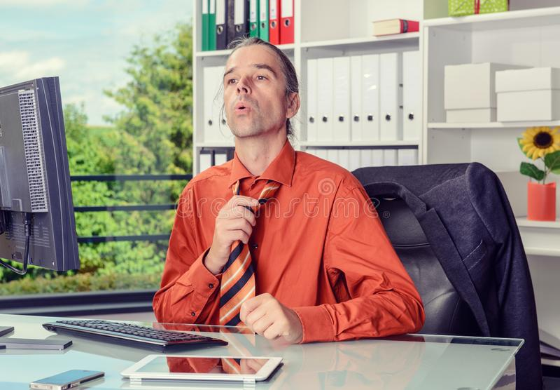 Jonge bedrijfsmens met ventilator bij zijn bureau in summerly heet o royalty-vrije stock foto's