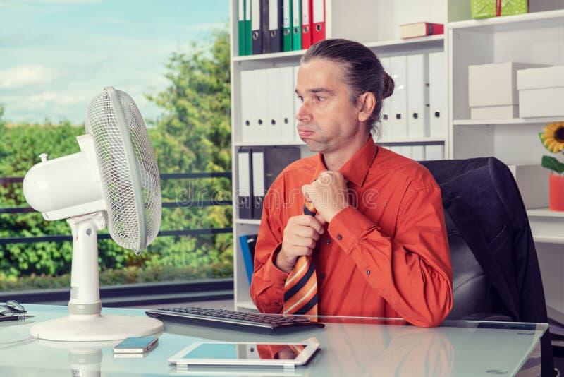 Jonge bedrijfsmens met ventilator bij zijn bureau in summerly heet o royalty-vrije stock afbeeldingen
