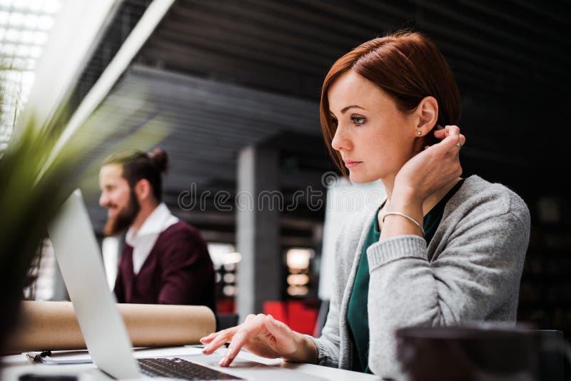 Jonge bedrijfsmensen die in bureau werken, die laptop met behulp van royalty-vrije stock foto
