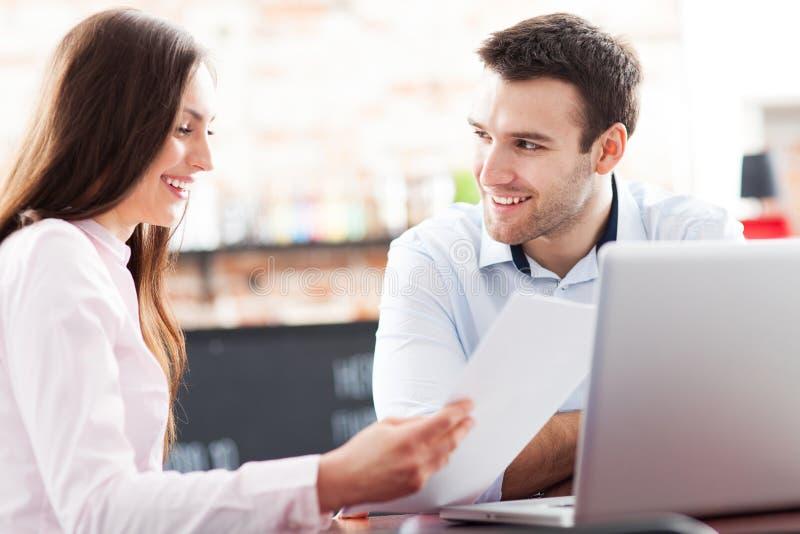 Bedrijfs mensen die laptop met behulp van bij koffie stock foto