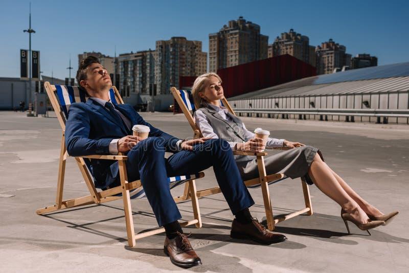 jonge bedrijfsmensen die op sunbeds met document koppen van koffie ontspannen stock foto's