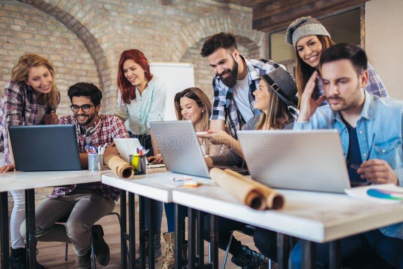 Jonge bedrijfsmensen die in slimme vrijetijdskleding in creatief bureau samenwerken royalty-vrije stock afbeeldingen