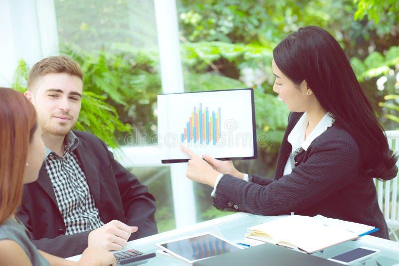 jonge bedrijfsmensen die vergadering maken en voor het analyseren van marketing het werken op kantoor spreken aan bureau royalty-vrije stock foto