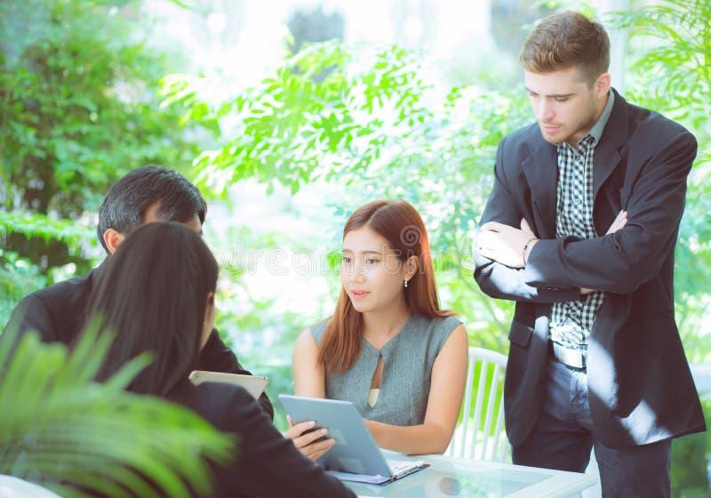 jonge bedrijfsmensen die vergadering maken en voor het analyseren van marketing het werken op kantoor spreken aan bureau stock afbeelding