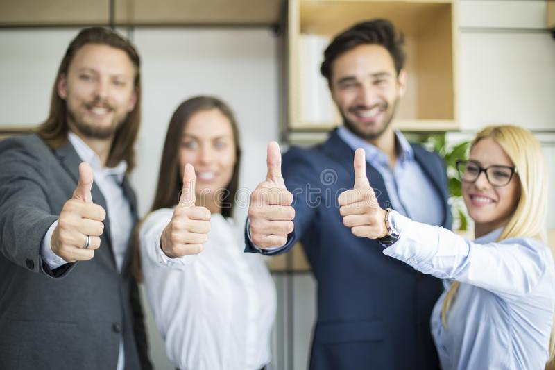 Jonge bedrijfsmensen met duim die in het bureau opstaan stock afbeelding