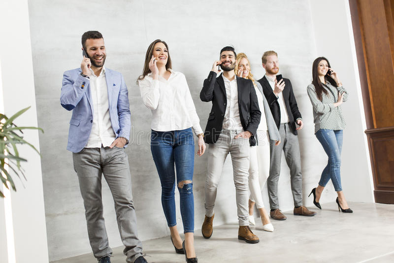 Jonge bedrijfsmensen met mobiele telefoons stock afbeelding