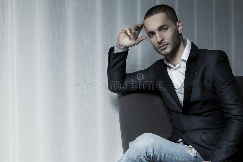 Jonge bedrijfsmensenzitting op een stoel en het bekijken de camera royalty-vrije stock fotografie