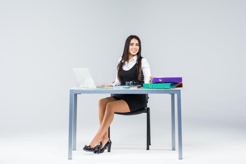 Jonge bedrijfsvrouw aan het werkende die lijstwerk aangaande laptop op grijze achtergrond wordt geïsoleerd stock afbeeldingen