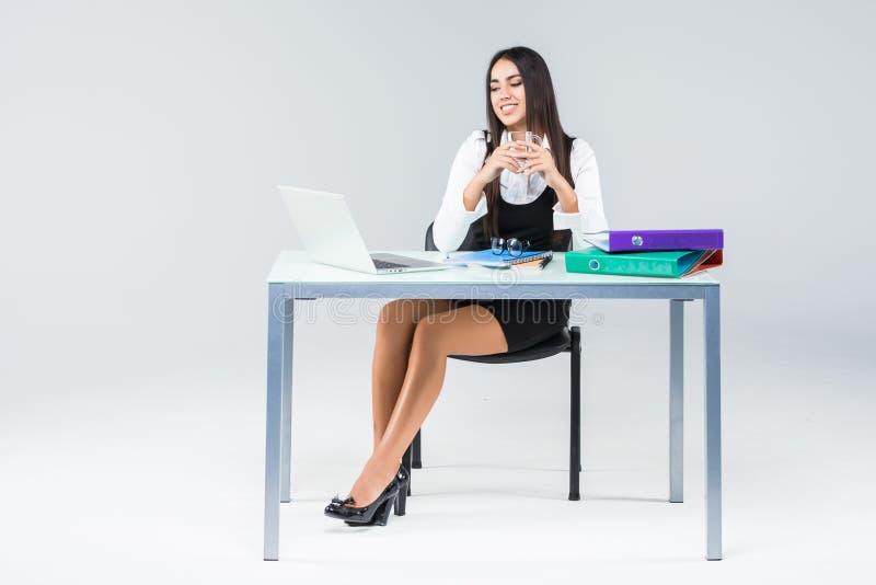 Jonge bedrijfsvrouw aan het werkende die lijstwerk aangaande laptop op grijze achtergrond wordt geïsoleerd royalty-vrije stock foto's