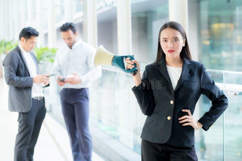 Jonge bedrijfsvrouw die bij de megafoon van de bureauholding werken royalty-vrije stock foto