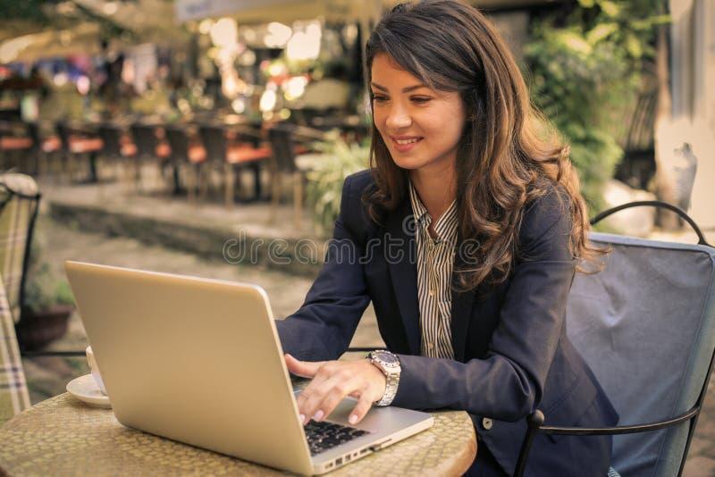 Jonge bedrijfsvrouw die bij koffie aan laptop werken stock foto