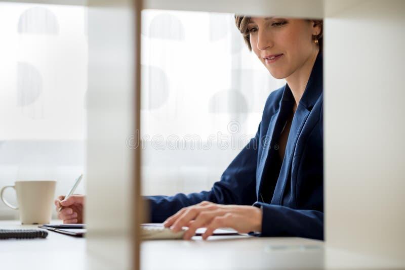 Jonge bedrijfsvrouw die calculator gebruikt royalty-vrije stock foto