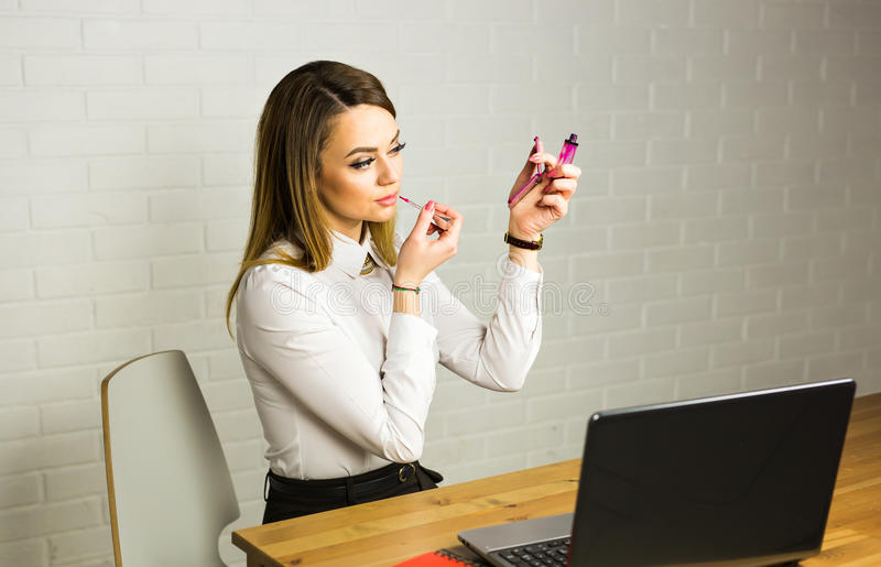 Jonge bedrijfsvrouw die in de spiegel kijken en lippenstift gebruiken bij haar worlplace royalty-vrije stock afbeelding