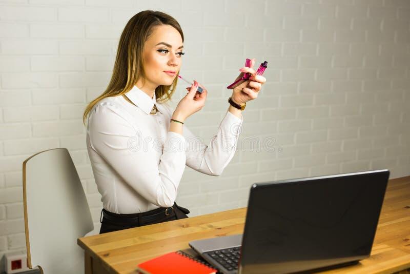 Jonge bedrijfsvrouw die in de spiegel kijken en lippenstift gebruiken bij haar worlplace stock fotografie