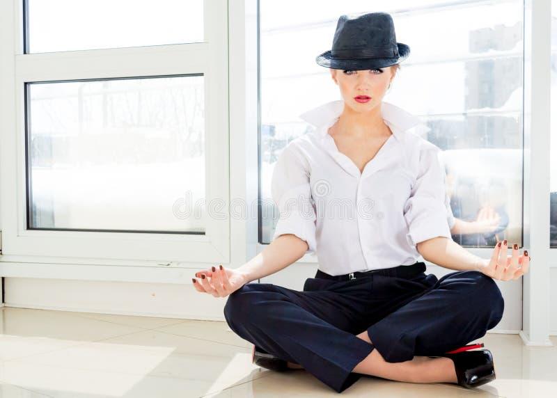 Jonge bedrijfsvrouw die dragend wit overhemd, hoed in bureau mediteren royalty-vrije stock foto