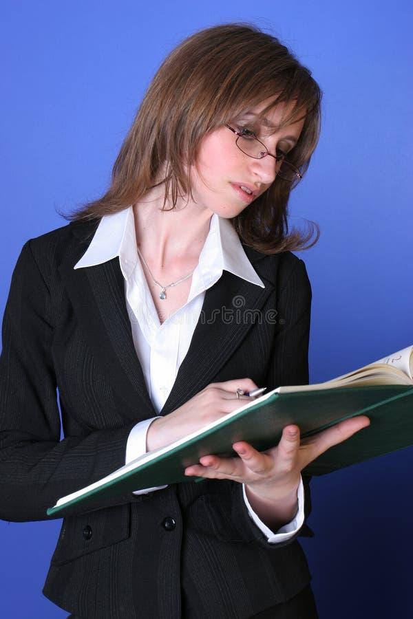Jonge bedrijfsvrouw die een groen dossier leest stock foto's