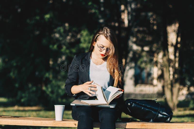 Jonge bedrijfsvrouw die in het park, het drinken koffie werken en het doorbladeren haar notitieboekje royalty-vrije stock fotografie