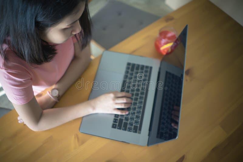 Jonge bedrijfsvrouw die laptop computer met behulp van die aan houten lijst met exemplaarruimte werken Het Aziatische meisje type royalty-vrije stock afbeelding