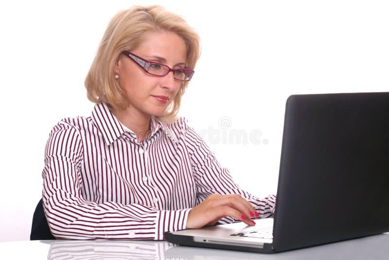 Jonge bedrijfsvrouw die laptop met behulp van bij het werkbureau stock afbeelding
