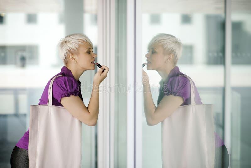Jonge bedrijfsvrouw die make-up in de straat toepassen royalty-vrije stock fotografie