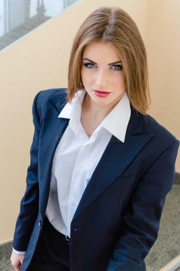 Jonge bedrijfsvrouw die man kostuum in bureau dragen royalty-vrije stock foto's