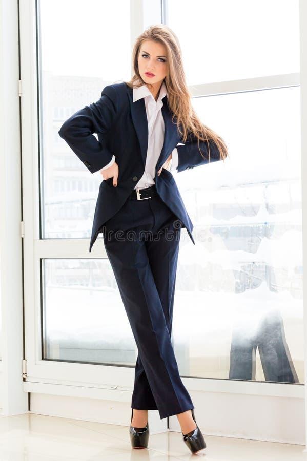 Jonge bedrijfsvrouw die man kostuum en hoge hielen in bureau dragen royalty-vrije stock afbeelding