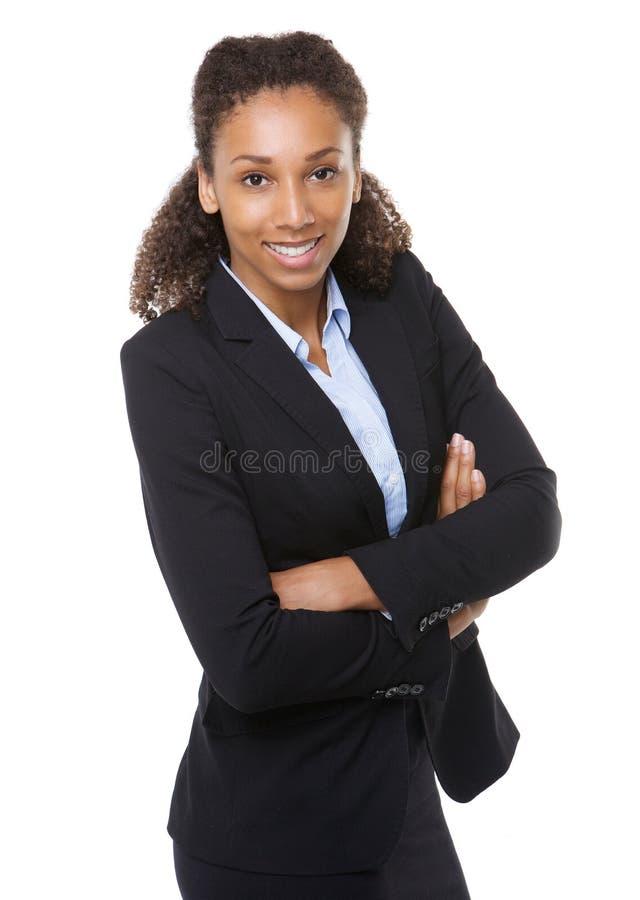 Jonge bedrijfsvrouw die met gekruiste wapens glimlachen stock foto