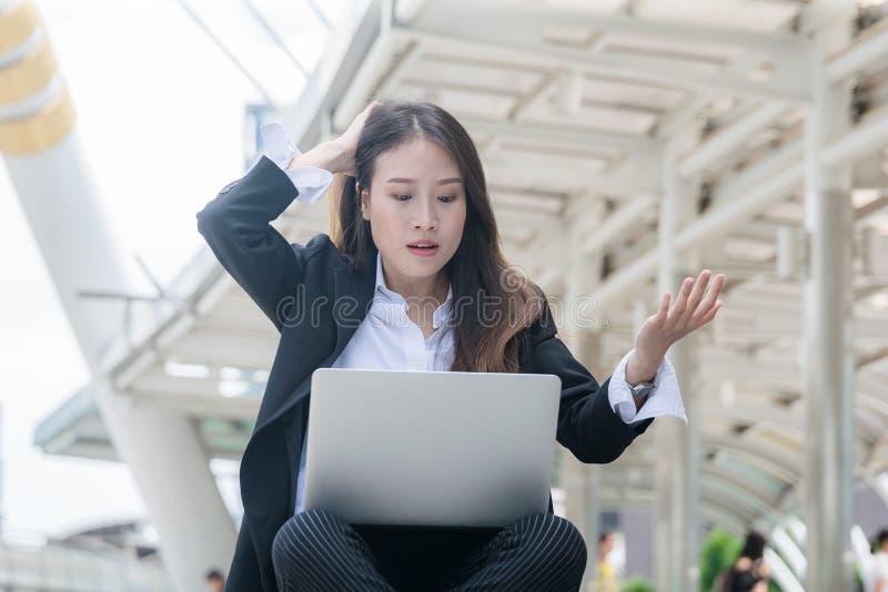 Jonge bedrijfsvrouw die met laptop werken die laptop notitieboekje met geschokte negatieve spanningshouding kijken royalty-vrije stock afbeeldingen